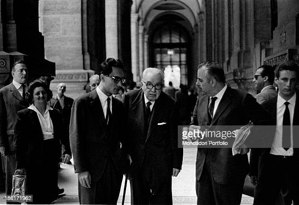 The lawyer and jurist Francesco Carnelutti in a portico not far from the Palace of Justice is leaning on his stick surrounded by his substitute the...