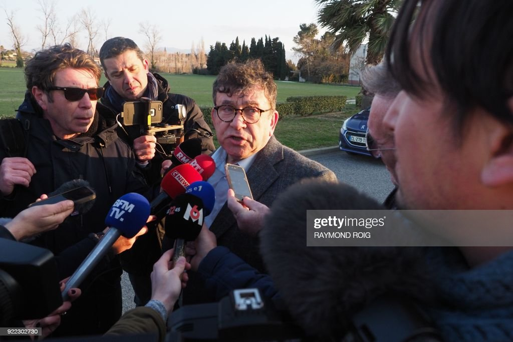 The lawyer of a schoolbus driver - who was involved in an accident in December 2017 - Jean Codognes (C) speaks with media representatives after a hearing at Theza on February 21, 2018. The driver of the school bus involved in the collision with a regional train in December in Millas (Pyrénées-Orientales) has on February 21, 2018, maintained his version of the 'barrier raised' during his hearing at Théza, near Perpignan, before the two judges of investigation in charge of the investigation into the accident that killed six, said his lawyer. /