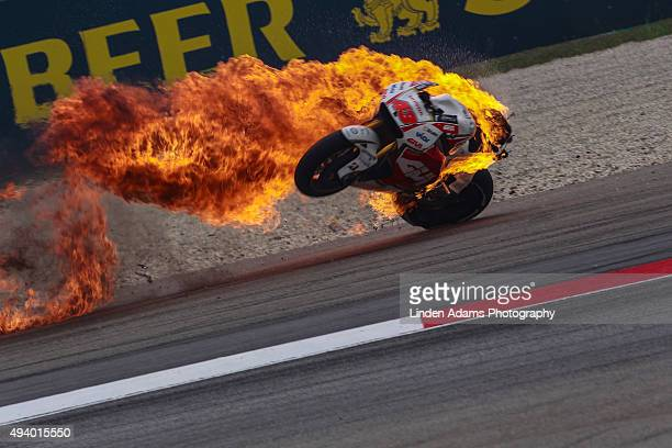 The LCR Honda bike of Australian rider Jack Miller bursts into flames at Sepang Circuit on October 24 2015 in Kuala Lumpur Malaysia