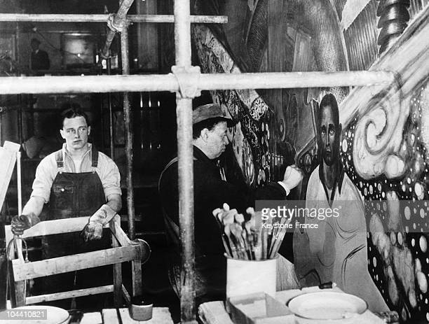 The leader John F CURRY's grandnephew Hugh CURRY Jr posing for a big fresco the Mexican artist Diego RIVERA was making in the hall of Rockefeller...
