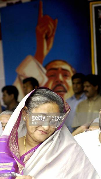 The leader of Bangladesh's main opposition party the Awami League Sheikh Hasina Wajed writes a speech in front of a portrait of her father Sheikh...