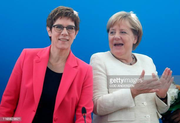 The leader of Germany's conservative Christian Democratic Union party Annegret KrampKarrenbauer and German Chancellor Angela Merkel are pictured...