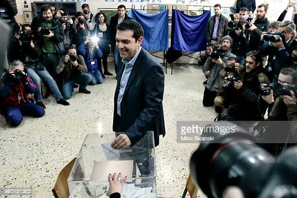 The leader of Greece's leftwing Syriza party Alexis Tsipras casts his ballot at a polling station in a school in a suburb of Athens on January 25...