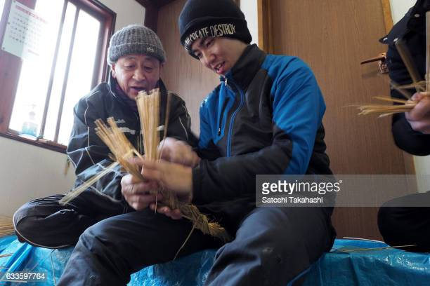 The leader of Namahage players at Sugoroku district Mikio Miura who teaches a young Namahage player Kyosuke Shinoda how to make Kede which is...