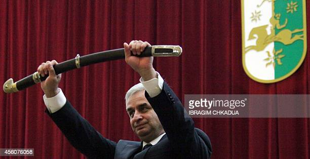 The leader of the Abkhazian opposition and presidentelect Raul Khadjimba holds a sword as he takes his oath of office duting the inauguration...