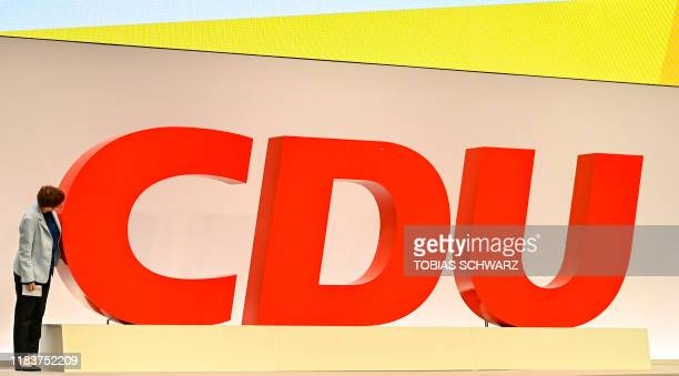 The leader of the Christian Democratic Union Annegret KrampKarrenbauer leans on her party's logo as she tours the venue before the start of their...