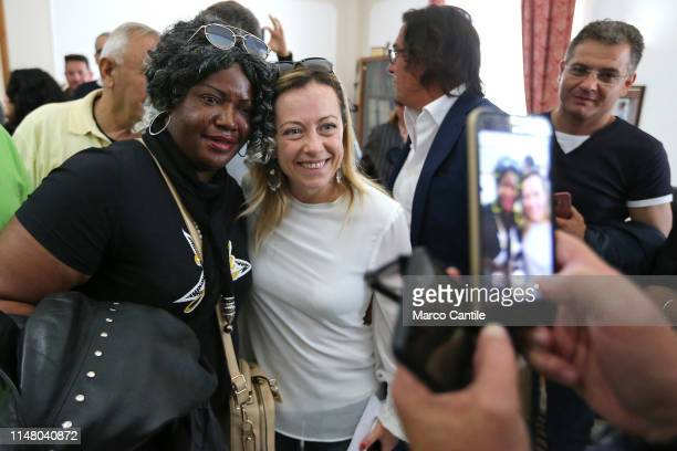 The leader of the political party Fratelli d'Italia Giorgia Meloni takes a picture with an immigrant woman at the end of a political meeting in...