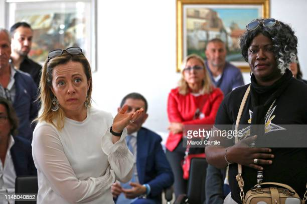 The leader of the political party Fratelli d'Italia Giorgia Meloni speaks with an immigrant woman during a political meeting in Castel Volturno for...