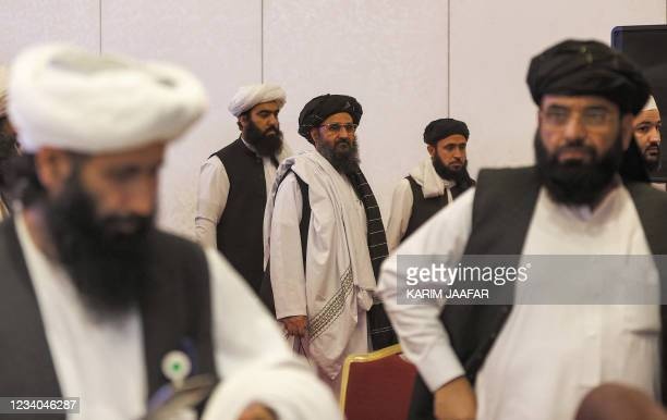 The leader of the Taliban negotiating team Mullah Abdul Ghani Baradar walks after the final declaration of the peace talks between the Afghan...