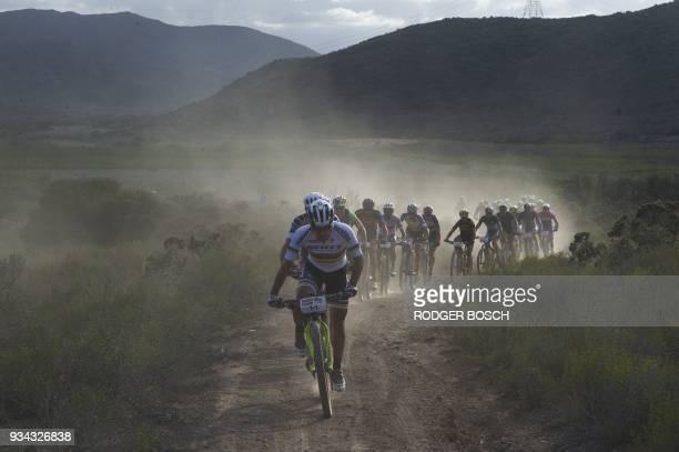 TOPSHOT The leading pack of professional riders kick up a cloud of dust as they ride during the first full stage of the 2018 Cape Epic African...