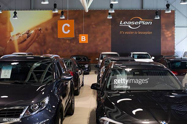 The LeasePlan Corp logo sits on a sign as automobiles sit on display inside the company's used car leasing and contract hire showroom in Breukelen...