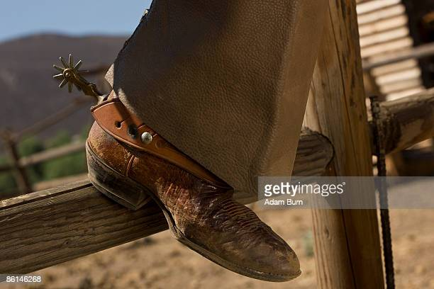 The leather boot of a cowboy resting on a fence
