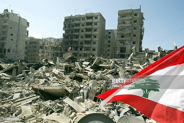 The Lebanese flag flies 14 August 2006 over the rubble of buildings hit in Israeli strikes in the Hezbollah stronghold of Beirut southern suburb A...
