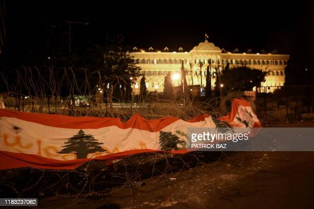 The Lebanese flag hangs on barbed wires protecting the Grand Serail or government building in downtown Beirut on November 18 2019 An unprecedented...
