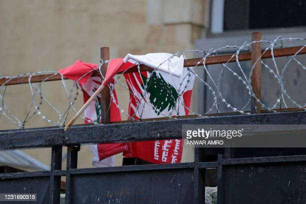 The Lebanese flag is pictured tangled on the barbed wire of a fortified gate, leading to the Lebanese Parliament building, in downtown Beirut on...