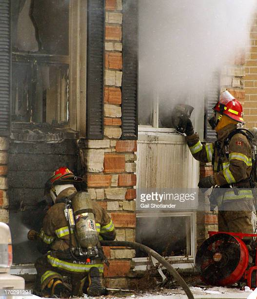 The left fireman is putting out hotspots with a hose attached to the local water source. The right fireman is testing the heat levels with his gauge....