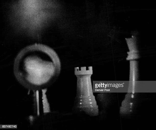 The left photograph of a hologram shows pieces of a chess set slightly out of alignment A small magnifying glass left is placed in front of knight...