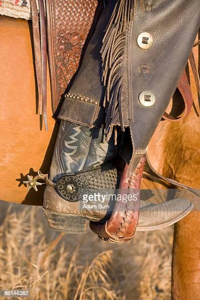 the leg of a cowboy in a horse stirrup - pantalón de cuero fotografías e imágenes de stock