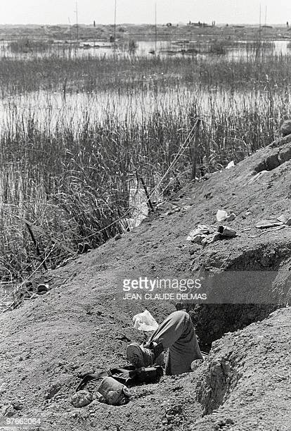 The leg of an Iranian soldier sticks out 22 March 1985 from a trench in a swamp near the Iraqi city of alHoweizah north of Basra after a fierce...