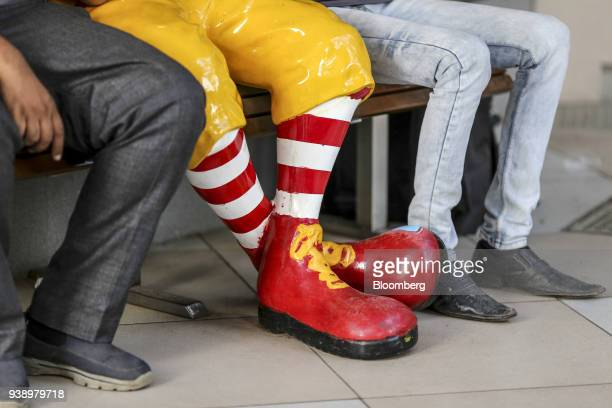 The legs and feet of food delivery couriers and a statue of Ronald McDonald are seen outside a McDonald's Corp restaurant operated by Hardcastle...