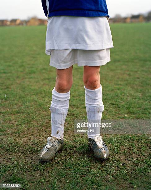 The legs of a child dressed for soccer