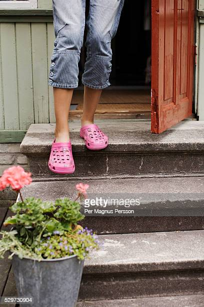 The legs of a woman walking down the stairs