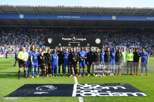 The Leicester City and Bournemouth players stand with the match officials in protest against racism prior to the Premier League match between...