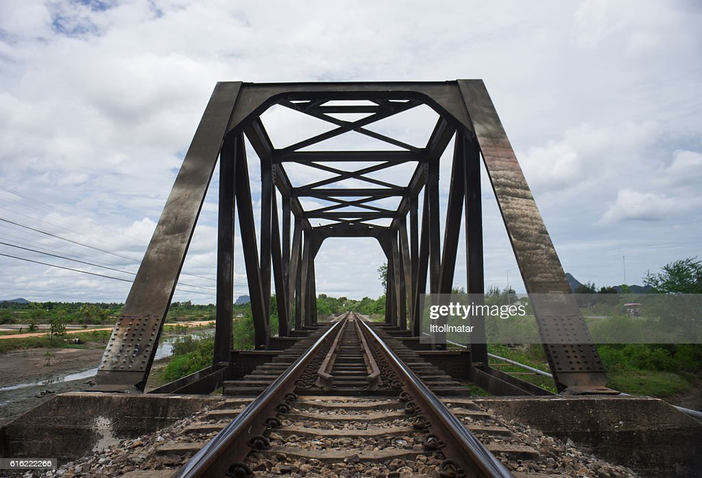 the length of railway with old steel bridge : Stock Photo