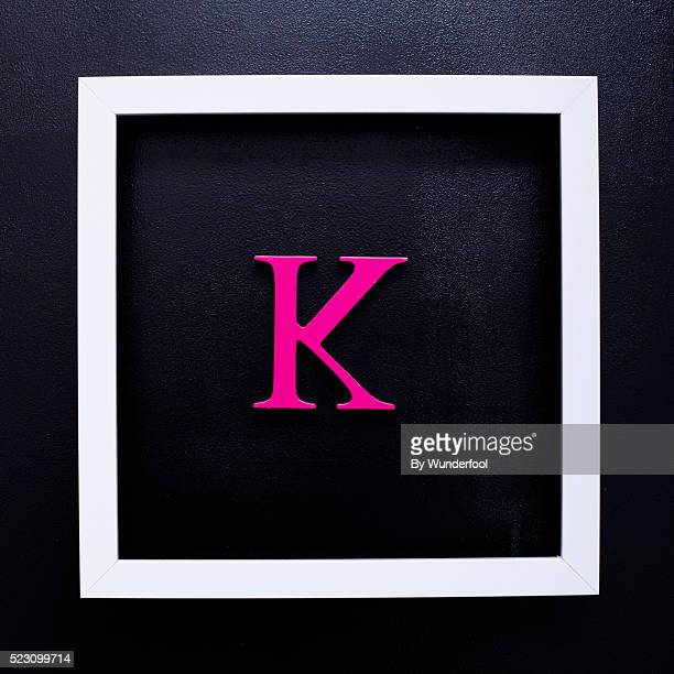 The Letter K in pink wood seen from above on a black background