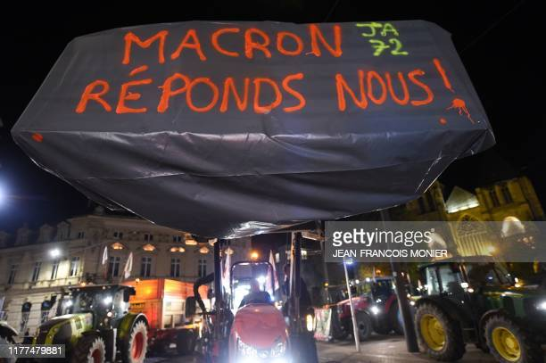 TOPSHOT The lettering on a canvas reads 'Macron answer us' as farmers demonstrate in front of the Prefecture of the Sarthe during a demonstration...