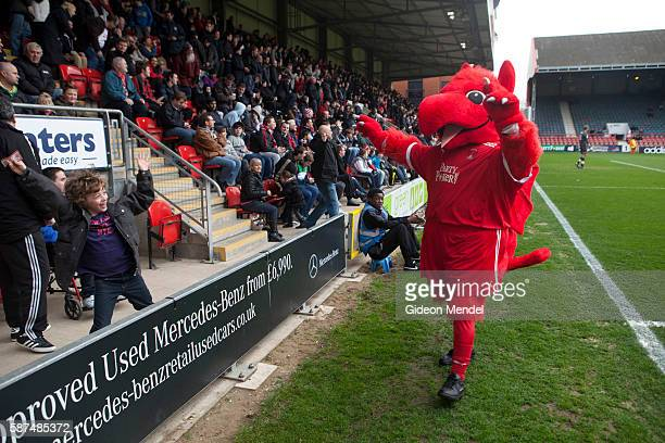 The Leyton Orient football dragon mascot celebrates with fans shortly after their team scored a goal against Brentford This was during a home game at...