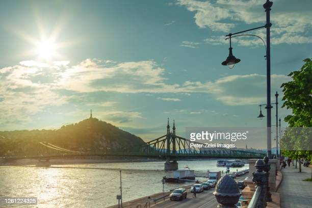 the liberty bridge and the gellert hill in budapest, hungary at sunset - hungary stock pictures, royalty-free photos & images