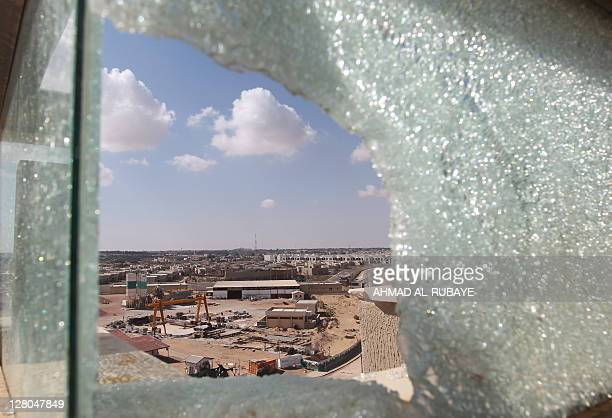 The Libyan city of Sirte appears behind the shattered glass of AlKardabiya Hotel where Libyan National Transitional Council fighters have taken...