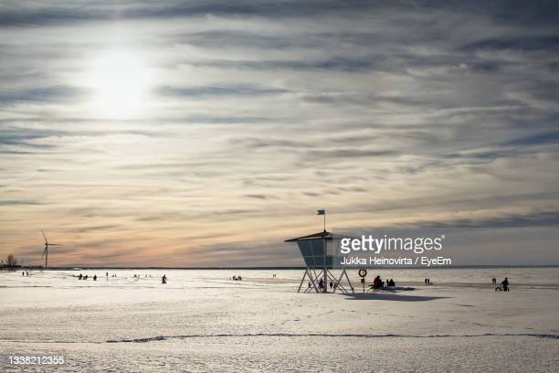 the life guard's hut is standing in guard while people are enjoying a beautiful day on the seaside. - heinovirta stock pictures, royalty-free photos & images