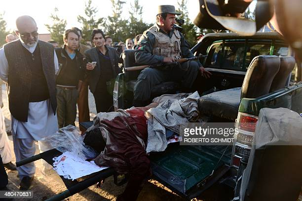 The lifeless body of a Taliban fighter is taken away by police from the site of a deadly attack on an Afghan election commission office in Kabul on...