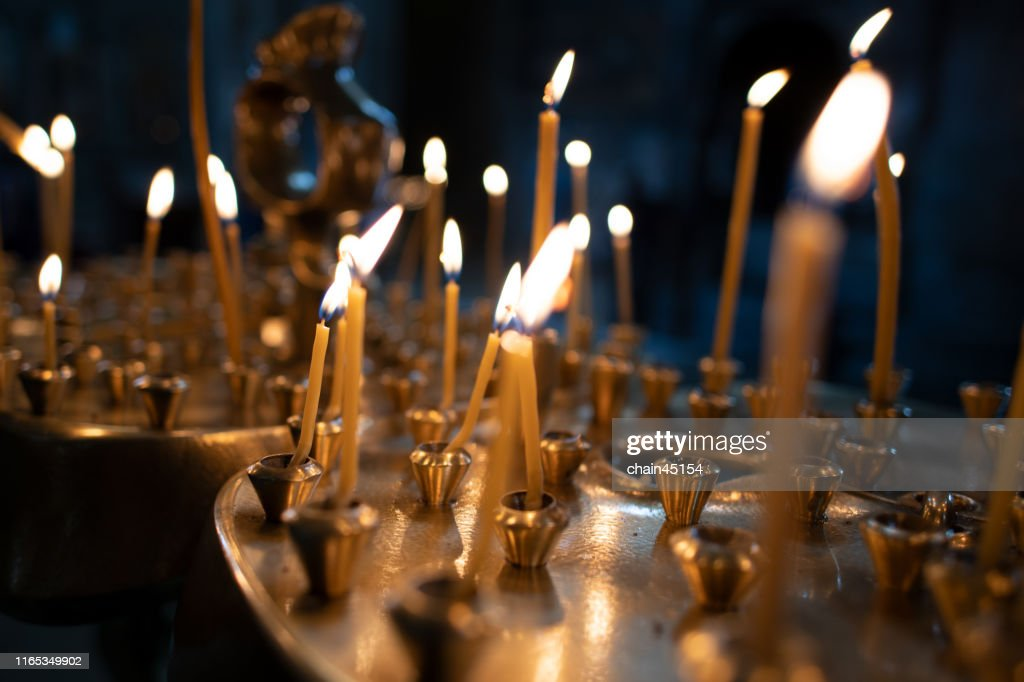 The light on candles in the church with the dark tone of background for praying to the God : ストックフォト