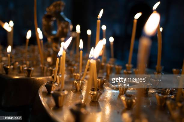 the light on candles in the church with the dark tone of background for praying to the god - candle of hope stock pictures, royalty-free photos & images