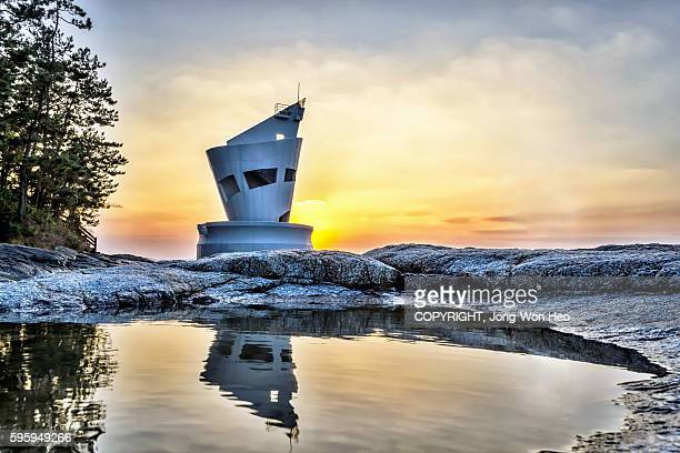 The lighthouse under the sunset and its reflection on the puddle