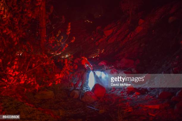 The lights of a firetruck illuminate a firefighter dowsing a hot spot at the Thomas Fire on December 16 2017 in Montecito California The National...