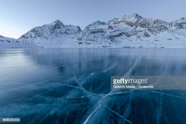 the lights of dusk on frozen lago bianco switzerland - see stock-fotos und bilder