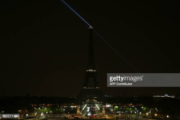 TOPSHOT The lights of the Eiffel Tower in the French capital Paris are switched off on October 16 in homage to the victims of an attack two days ago...