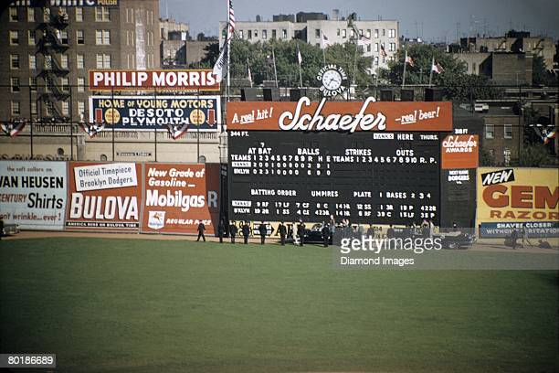 The limousine carrying President Dwight Eisenhower enters Ebbets Field and proceeds along the warning track in front of the main scoreboard prior to...