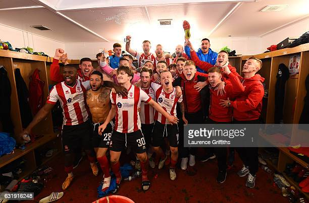 The Lincoln team and staff celebrate their victoary in the changing room after the Emirates FA Cup third round replay between Lincoln City and...