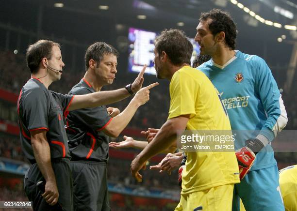 The linesman tells Villarreal's goalkeeper Diego Lopez to back off as referee Wolfgang Stark issue's Villarreal's Sebastian Eguren with a red card