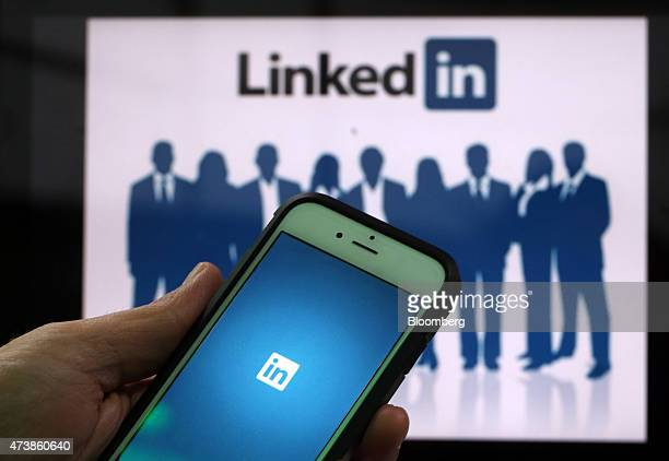 The LinkedIn Corp logo is displayed on the screens of an Apple Inc iPhone 6 and a laptop in this arranged photograph taken in London UK on Friday May...