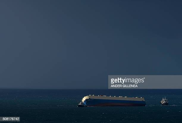 TOPSHOT The listing Panamanianregistered cargo ship 'Modern Express' is towed by a Spanish tugboat into the port of the Spanish northern Basque city...