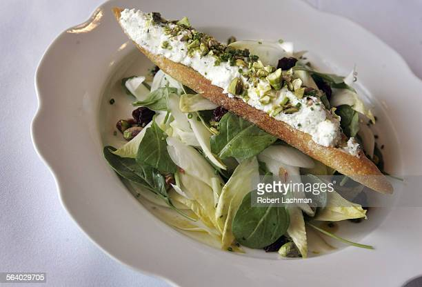 The Literati Salad with organic endive and arugula served with dried cherries pistachios a lemon vinaigrette and topped with a goat cheese crouton at...