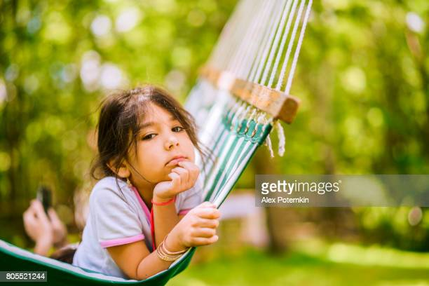 The little 5-years-old girl resting and have fun in the hammock in the park