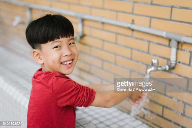 The little Asian boy washes his hands on the washstand.