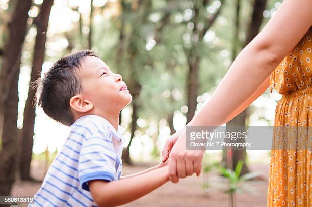 The little boy and mother holding hands.